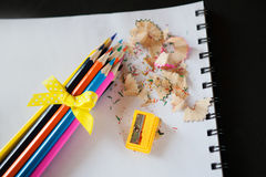 Grupp av kulöra blyertspennor som vässas med en gula pilbåge, vässare och shavings Fotografering för Bildbyråer