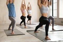 Grupp av kursen för ungdomarden övande yoga, krigare som jag poserar arkivfoton