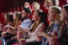 Grupp av kvinnlig hållande ögonen på komedi i bio royaltyfri bild