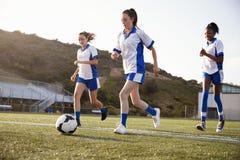 Grupp av kvinnliga högstadiumstudenter som spelar i fotbolllag arkivbild