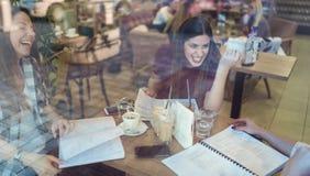 Grupp av kvinnliga studenter som ler som talar i coffee shop efter grupper royaltyfria foton