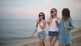 Grupp av kvinnliga vänner som har gyckel som tycker om en dryck på stranden vid havet på solnedgången i ultrarapid Unga kvinnor arkivfilmer