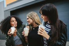 Grupp av kvinnliga vänner som har iskaffe utomhus arkivbild