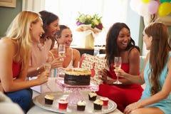 Grupp av kvinnliga vänner som hemma firar födelsedag royaltyfri bild