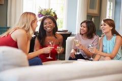 Grupp av kvinnliga vänner som hemma kopplar av med drinkar fotografering för bildbyråer