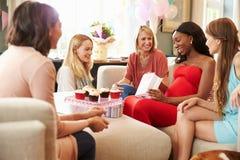 Grupp av kvinnliga vänner som möter för baby shower hemma arkivbilder