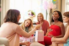 Grupp av kvinnliga vänner som möter för baby shower hemma Arkivfoton