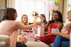 Grupp av kvinnliga vänner som möter för baby shower hemma arkivfoto
