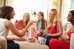 Grupp av kvinnliga vänner som möter för baby shower hemma royaltyfri foto