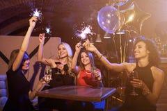 Grupp av kvinnliga vänner som tycker om födelsedagpartiet som har gyckel med fyrverkeritomtebloss som dricker alkoholiserat sitta arkivbild