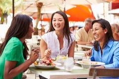 Grupp av kvinnliga vänner som tycker om lunch i utomhus- restaurang Royaltyfri Fotografi