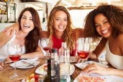 Grupp av kvinnliga vänner som tycker om mål i utomhus- restaurang arkivfoto