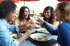 Grupp av kvinnliga vänner som tycker om mål på den utomhus- restaurangen Arkivfoto
