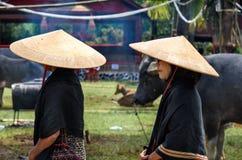 Grupp av kvinnor i svarta och koniska sugrörhattar på begravnings- ceremoni Tana Toraja Arkivbilder