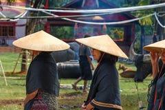 Grupp av kvinnor i svarta och koniska sugrörhattar på begravnings- ceremoni Tana Toraja Arkivfoton