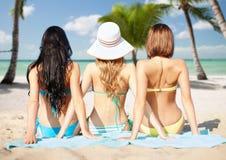 Grupp av kvinnor i swimwear som solbadar på stranden Arkivbild