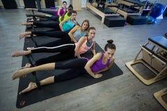 Grupp av kvinnor som övar med pilatescirkeln royaltyfri bild