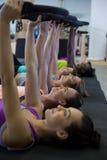 Grupp av kvinnor som övar med pilatescirkeln fotografering för bildbyråer