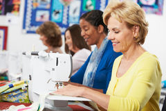 Grupp av kvinnor som använder elektriska symaskiner i grupp Arkivfoto