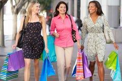 Grupp av kvinnor som bär shoppingpåsar på stadsgatan Fotografering för Bildbyråer