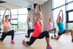 Grupp av kvinnor som gör utfallet att öva i idrottshall Arkivbilder
