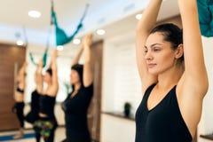 Grupp av kvinnor som gör yogaövningar i idrottshall Passform- och wellnesslivsstil royaltyfri bild