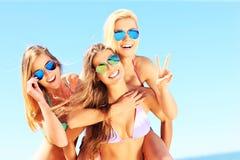 Grupp av kvinnor som har gyckel på stranden royaltyfri fotografi