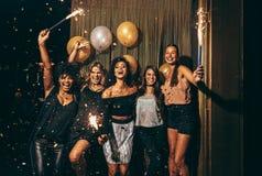 Grupp av kvinnor som har partiet på nattklubben royaltyfri bild