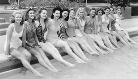 Grupp av kvinnor som i rad sitter på pölsidan (alla visade personer inte är längre uppehälle, och inget gods finns Leverantörwarr Royaltyfria Bilder