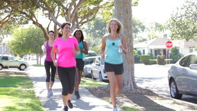 Grupp av kvinnor som joggar ner den stads- gatan stock video