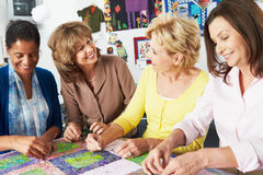 Grupp av kvinnor som tillsammans gör täcket Arkivfoton
