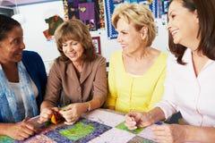 Grupp av kvinnor som tillsammans gör täcket Arkivfoto