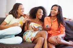 Grupp av kvinnor som tillsammans sitter på Sofa Watching TV Royaltyfria Bilder