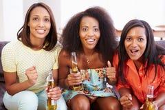 Grupp av kvinnor som tillsammans sitter på Sofa Watching TV Arkivfoton