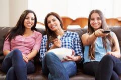 Grupp av kvinnor som tillsammans sitter på Sofa Watching TV Arkivfoto