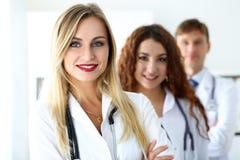 Grupp av läkare som poserar proudly i rad och in camera ser arkivbild