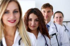 Grupp av läkare som poserar proudly i rad och in camera ser smil arkivfoto
