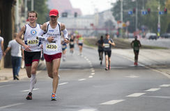 Grupp av löpare i gator som kör under maraton Arkivfoton