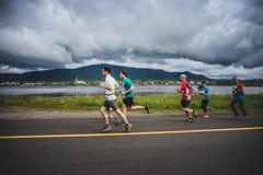 Grupp av löpare 10K framme av ett härligt berglandskap Arkivfoto