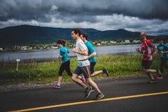 Grupp av löpare 10K framme av ett härligt berglandskap Royaltyfria Bilder