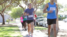 Grupp av löpare som joggar ner den stads- gatan arkivfilmer