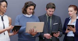 Grupp av ledare som använder bärbara datorn och den digitala minnestavlan 4k arkivfilmer
