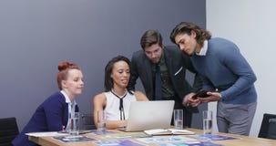 Grupp av ledare som diskuterar över bärbara datorn på skrivbordet 4k stock video
