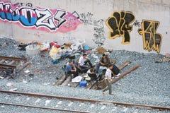 Grupp av lokala män som ut hänger bredvid järnväg Arkivfoto