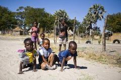 Grupp av lokala ungar som samlas för att spela fotografering för bildbyråer