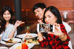 Grupp av lyckliga asiatiska manliga och kvinnliga vänner som tillsammans tar ett selfiefoto och har ett socialt rostat bröd i res arkivfoto