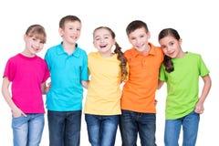 Grupp av lyckliga barn i färgrika t-skjortor. Arkivfoton