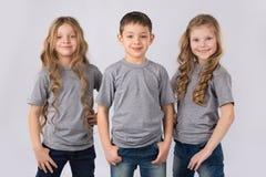 Grupp av lyckliga barn i gråa t-skjortor som isoleras på vit bakgrund Arkivbild