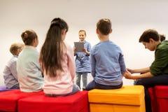 Grupp av lyckliga barn med minnestavlaPC på skolan fotografering för bildbyråer