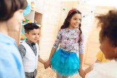 Grupp av lyckliga barn som dansar rund dans på födelsedagpartiet Begrepp av ferie för barn` s Arkivbilder
